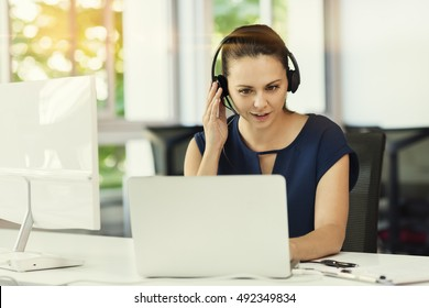 Young business woman in video conference at the modern office space. Big windows and trees background