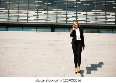 Young business woman walk on stairs leaving office building and talk on a phone .