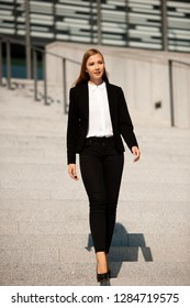 Young business woman walk on stairs leaving office building .