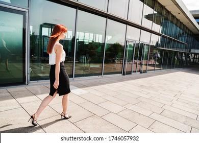 Young business woman walks along modern building