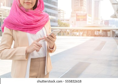 Young  business woman wear head scarf using cell phone  in city