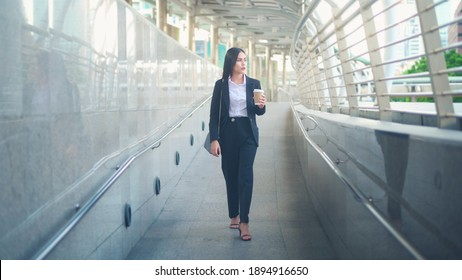 A young business woman wearing black suit is using smart phone , holding a cup of coffee in the city, Business Lifestyle Concept
