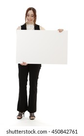 Young business woman wearing a business suit with a happy expression looking down on a white board against white background