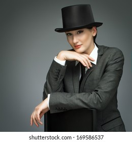 048b4789e7d Young business woman wearing top hat over grey background. Woman feels like  a man -