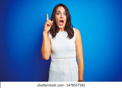 Young business woman wearing white elegant dress standing over blue isolated background pointing finger up with successful idea. Exited and happy. Number one.