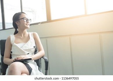 Young business woman in white dress who is candidate sitting wait for interview while looking out of big window. With copy space.