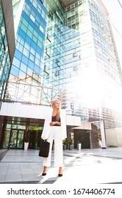 Junge Geschäftsfrau in weißem Anzug draußen