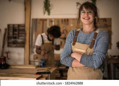 Young business woman working as carpenter in a small carpentry workshop. Couple of carpenters working together designing new home furniture design. Small family business concept of young entrepreneurs