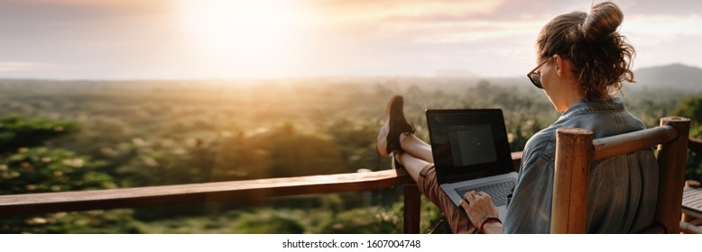 Young business woman working at the computer in cafe on the rock. Young girl downshifter working at a laptop at sunset or sunrise on the top of the mountain to the sea, working day. - Shutterstock ID 1607004748