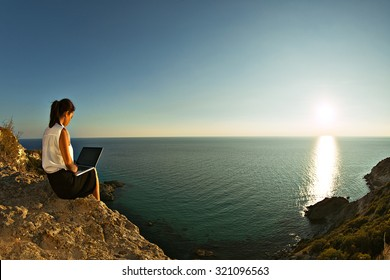 Young business woman working at the computer on the beach on the rock face. Young girl downshifter working at a laptop at sunset or sunrise on the top of the mountain to the sea, working day.