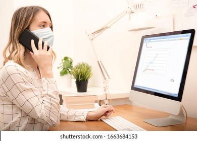 Young business woman working from home wearing protective mask