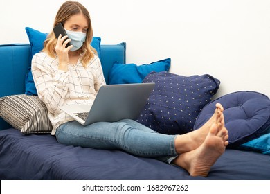Young business woman working from home with laptop and smartphone, wearing protective mask