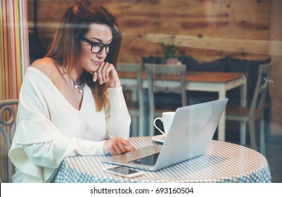 Young business woman working with laptop and mobile phone at cafe, freelance concept