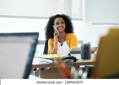 Young business woman working in modern office. Black businesswoman talking and smiling on mobile telephone. Busy African American employee using smartphone at work