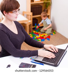 young business woman working on a laptop with her child playing at the back