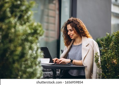Young business woman working on a computer outside the cafe