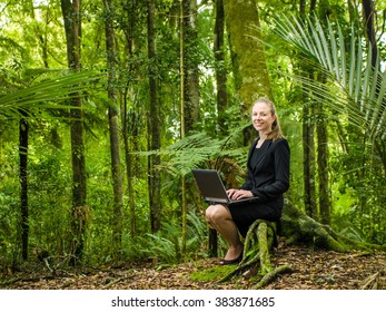 young business woman working on laptop in forest