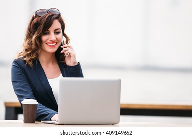 Young business woman working on laptop and talking on mobile phone