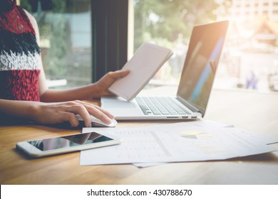 young business woman working on laptop computer hand holding notebook and smart phone on wood desk while sitting in coffee shop,  vintage filter