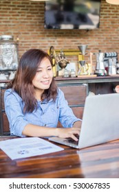 Young business woman working on laptop computer while sitting in vintage cafe bar.