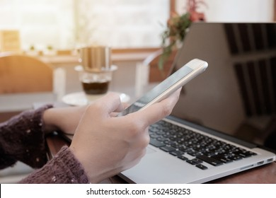 young business woman working on laptop computer hand holding smart phone on wood desk while sitting in coffee shop