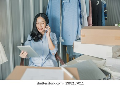 Young business woman working online e-commerce shopping at her shop. Young woman seller prepare parcel box of product for deliver to customer. Online selling, e-commerce.