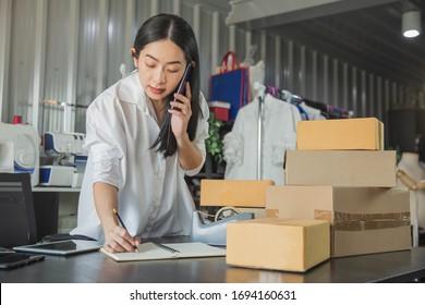 Junge Geschäftsfrau, die im Online-Handel in ihrem Geschäft einkauft. Junge Frau Verkäufer bereiten Paketschachtel für die Lieferung an den Kunden. Online-Verkauf, E-Commerce.
