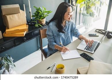 Junge Geschäftsfrau, die im Online-Handel in ihrem Geschäft einkauft. Junge Frau Verkäufer bereiten Paketschachtel für die Lieferung an den Kunden vor. Online-Verkauf, E-Commerce.