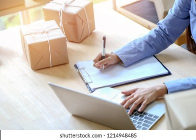 Young business woman was writing order on paper from labtop with carton delivery box on wooden desk, SME concept.