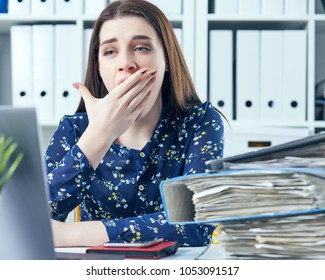 Young business woman yawning at a modern office desk in front of laptop, covering her mouth. Overworked woman.