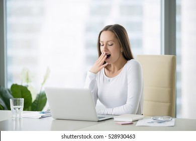 Young business woman yawning at a modern office desk in front of laptop, covering her mouth out of courtesy, chain reaction, drowsiness, unable to deal with boring job, monday after cool weekends
