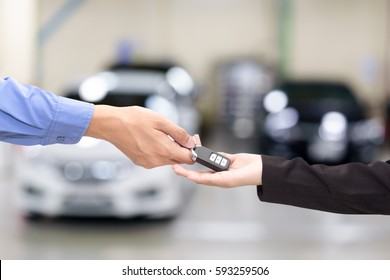 Young business women giving a key in font of car
