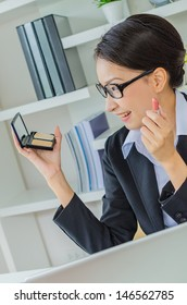 Young business women make up her face in office