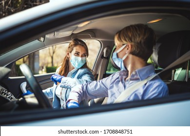 Young business women with protective masks on their faces are going to the work and bump elbows instead of greeting with a hug or handshake to avoid the spread of coronavirus.