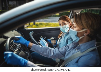 Young business women with protective masks on their faces are sitting in a car and talking about global crisis. They are showing each other an animation of a corona virus on a tablet.