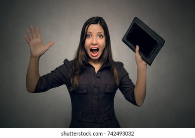 Young business women in stress and panic  with a wide open mouth holds a mobile tablet computer in her hands. Accountant. Annual report.