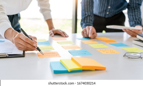young business workers posting with sticky notes stickers reminders  creative brainstorming at board the colleague in a modern co-working space