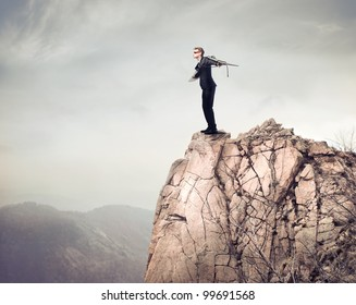 Young businessman about to fly from a mountain peak