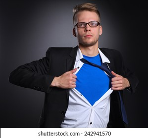 Young businessman acting like a super hero and tearing his shirt, standing