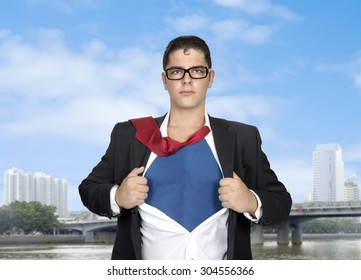 Young businessman acting like a super hero and tearing his shirt off with copy space