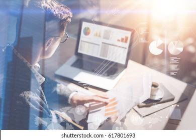 Young businessman analyze stock report on notebook screen.Concept of digital screen,virtual connection icon,diagram,graph interfaces on background.Double exposure