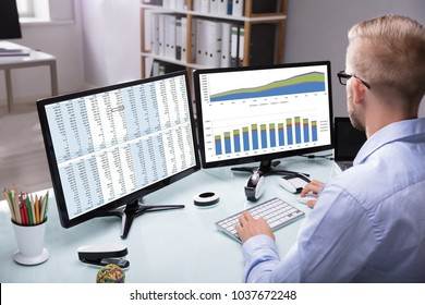 Young Businessman Analyzing Graph On Computer At Workplace