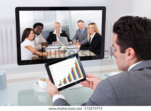 Young Businessman Analyzing Graph While Chatting With His Colleagues