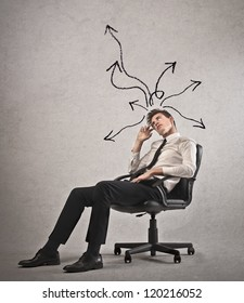 Young businessman with arrows in different directions on his head lying on a chair
