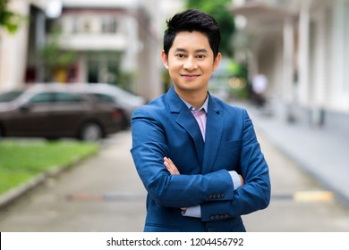 Young businessman Asian smiling and looking at camera. Portrait of a happy handsome young man on urban background. Young cool trendy man looking at camera