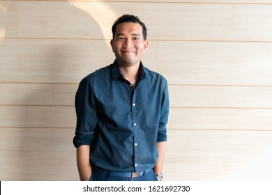 Young businessman asian smiling and looking at camera. Portrait of a happy handsome young man on wooden background. Close up face of young cool trendy man looking at camera