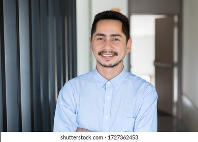 Young businessman asian smiling looking at camera. Portrait of a happy handsome young man in office. Close up face of young cool trendy man looking at camera.
