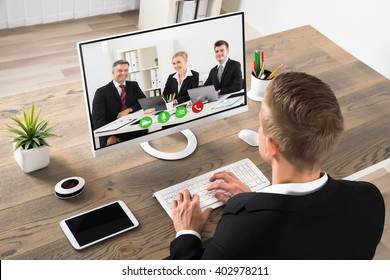 Young Businessman Attending Videoconference On Computer At Office