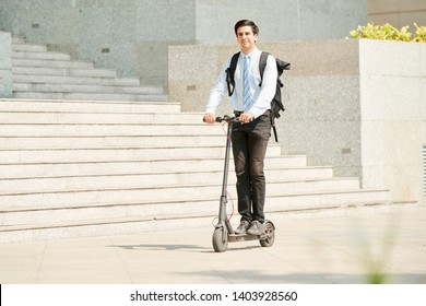 Young businessman with backpack on his back riding on scooter to work along the street in the city