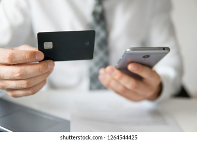 Young businessman with a bank credit card in his hands. Payment of goods online.